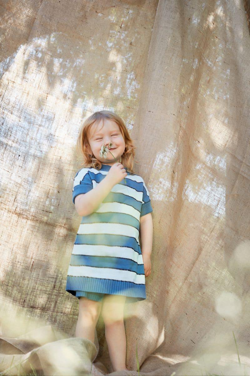 Mädchen in blau gestreiftem Strickkleid